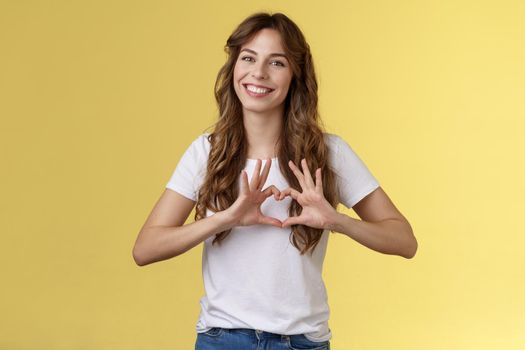 You my valantine. Tender confident adult girl curly hairstyle show heart gesture near chest express romantic sympathy feelings smiling delighted cherish relationship boyfriend yellow background