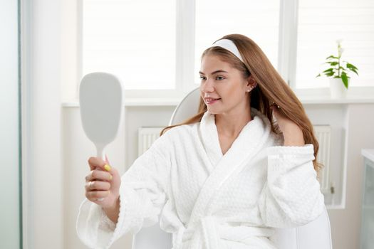 Woman in cosmetology salon satisfied with result of cosmetic procedure. Female looking at mirror and examining skin