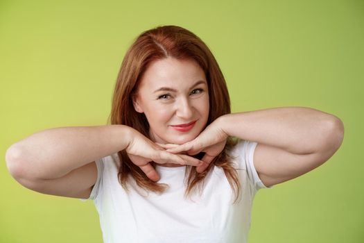 Aging, cosmetology, wellbeing concept. Happy self-assured redhead woman hold hands under jawline smiling showing facial blemished self-accepting wrinkles applying skincare product green background