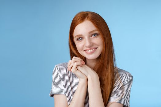 Tender romantic sincere young redhead teenage girl found love look sympathy delight press palms together cute pose smiling happily gazing camera passion lovely grin, blue background