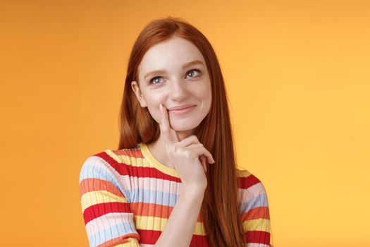 Happy tender feminine redhead 20s girl university student smiling delighted dreaming tasty slice pizza touching lip thoughtful, thinking daydreaming look upper left corner imaging desires