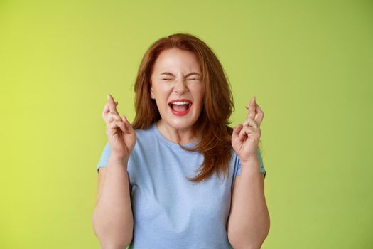 Woman wants win badly. Enthusiastic lucky redhead middle-aged 50s female pleading implore god make dream come true cross fingers good luck wishing closed eyes open mouth excitement green background