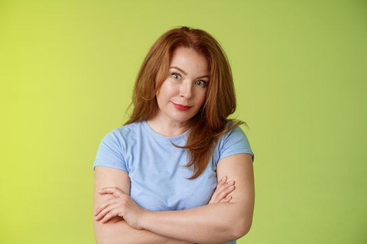 Confused shocked redhead mother look serious worried puzzled cross arms chest self-soothing calming gesture stare camera perplexed frustrated bad son behaviour stand green background disappointed