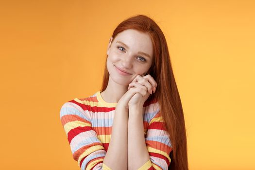 Dreamy sensual romantic young passionate redhead girlfriend melt heart feel sympathy joy receive sweet tender present lean palms smiling grateful gladly accept nice lovely gift, orange background