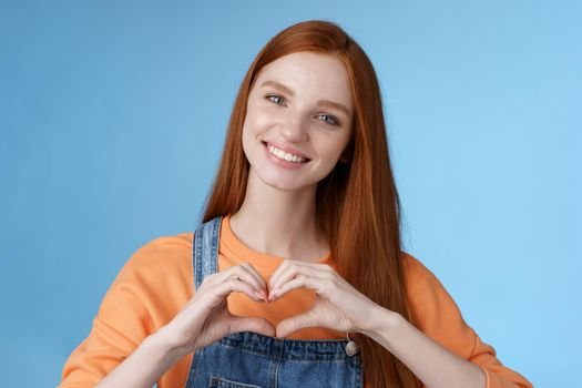 Love you. Attractive romantic tender redhead smiling gentle girlfriend blue eyes freckles show heart chest express sympathy romantic positive attitude confess passionate deep feelings, grinning cute