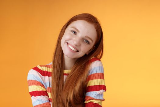 Tender lively cheerful smiling redhead european girl 20s tilting head leaning shoulder flirting grinning cute make lovely gazes camera coquettish talking boyfriend standing silly orange background