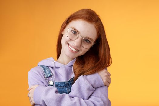 Passion, tenderness, wellbeing concept. Girl accept own self smiling charming grin tilt head hugging herself embracing body feel happiness delighted relaxing, flirty gaze camera orange background