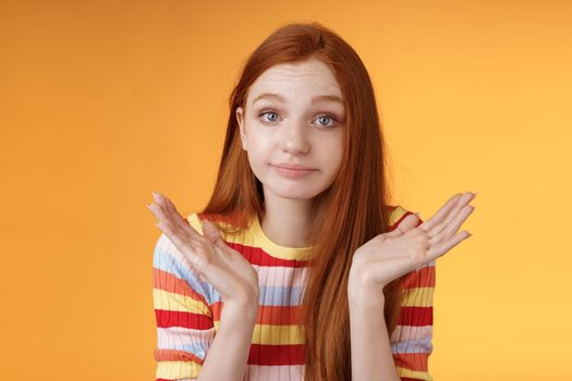 Clueless unbothered young redhead silly european girl 20s shrugging hands spread sideways smirking sorry cannot answer standing unaware confused puzzled give reply, orange background