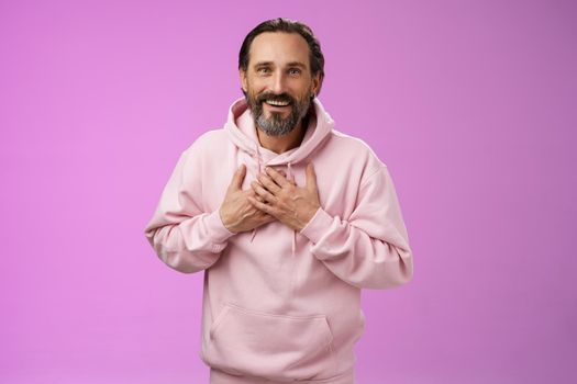 Thankful charming lucky adult bearded man 50s grey hair press palms heart receiving touching heartwarming gesture smiling grateful appreciating effort cherish moment, standing purple background