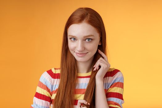 Romantic flirty shy attractive redhead girl 20s touching hair strand smiling silly modest glancing camera coquettish making lovely glances wanna seduce guy expressing sympathy, orange background