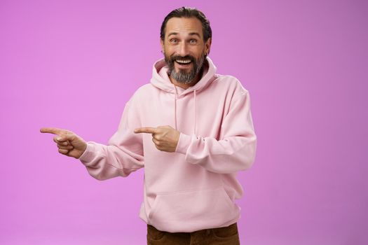 Charismatic happy good-looking mature 50s man wearing stylish hipster hoodie smiling excited pointing left index fingers impressed awesome interesting proposal standing pleased purple background