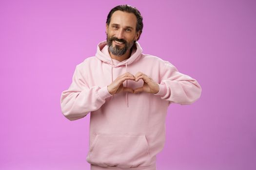 Family in heart. Portrait lovely handsome romantic bearded man in pink hoodie passionatly looking camera show love gesture smiling cute expressing romantic sympathy attitidue, purple background