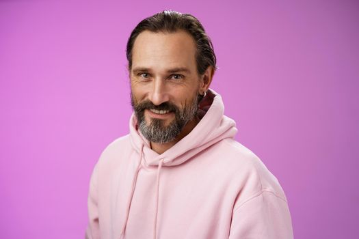 Charming alluring handsome bearded stylish adult male model earring pink hoodie smiling delighted express confidence positivity feel lucky amused, standing purple background talking casually