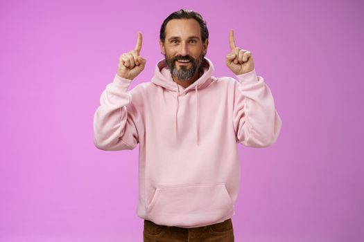 Handsome mature 50s man grey hair beard wearing stylish hipster loose hoodie pointing up index fingers showing awesome place hang out unwilling grow old standing positive lucky purple background