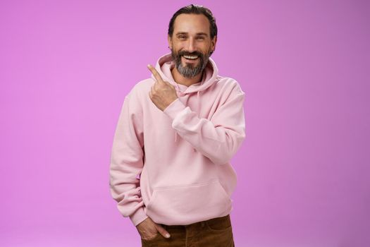 Charming friendly happy mature man 50s bearded grey hair laughing happily pointing upper left corner behind showing proudly family members standing purple background having fun stay positive