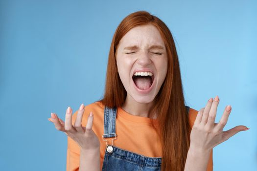 Pissed outraged moody redhead girl shouting complaining angry standing bothered screaming out loud close eyes yelling loudly raising hands sideways dismay full disbelief feel cheated painful betrayal