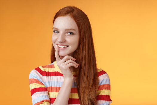 Curious devious redhead young 20s girlfriend have excellent idea smirking tricky touch lip flirty mysteriously glancing camera have plans preparing interesting surprise, standing orange background