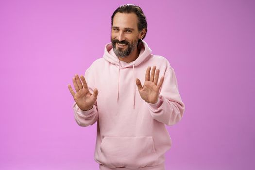 No thanks pass. Charming polite manly adult bearded man grey hair in pink hoodie apologizing refusal raise palms rejection gesture declining offer smiling say sorry not interested, purple background