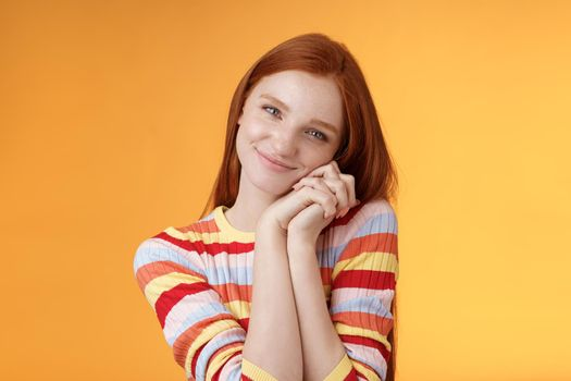 Sweet silly tender redhead young girl leaning palms touched smiling receive charming lovely gift standing thankful look affection sympathy accept dearest romantic gesture, orange background