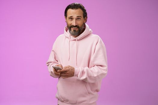 Stylish handsome adult bearded guy 40s in trendy pink hoodie holding smartphone texting look camera unbothered cool confident distracted playing awesome new app game, purple background