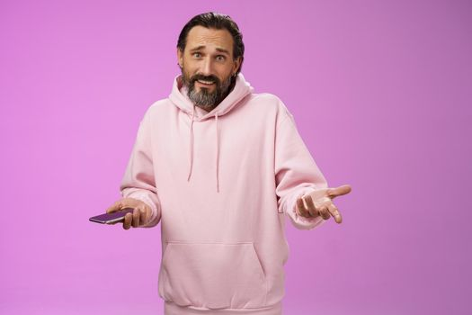 So what. Confused questioned adult bearded stylish guy in pink hoodie shrugging hands spread sideways dismay holding smartphone look clueless unaware camera not know how deal annoying phone calls