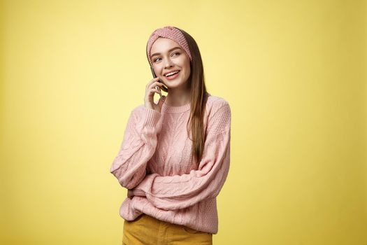 Talkative attractive glamour young 20s european woman wearing sweater, knitted headband tilting head looking away smiling curious, enjoying pleasant conversation via smartphone, talking to friend