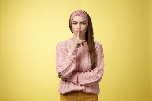 Keep mouth shut. Serious-looking bossy attractive young 20s woman in sweater, headband shushing making shhh gesture holding index finger on lips, gossiping, spread rumors over yellow background