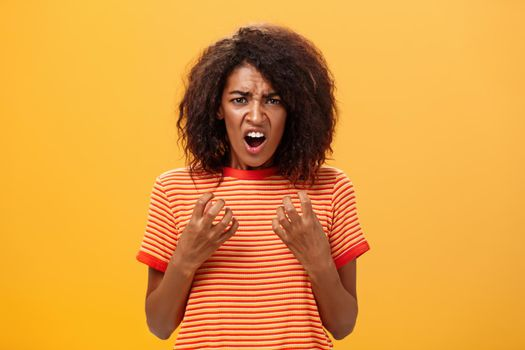 Waist-up shot of woman feeling upset feeling unfair things happened complaining and whining with regret frowning gesturing with palms near breast standing over orange background