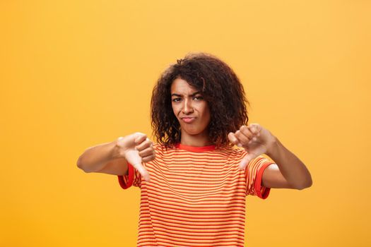 You loser and idea sucks. Dissatisfied and displeased young creative female artist with curly hairstyle frowning, sulking showing thumbd down in dislike gesture giving negative answer over orange wall