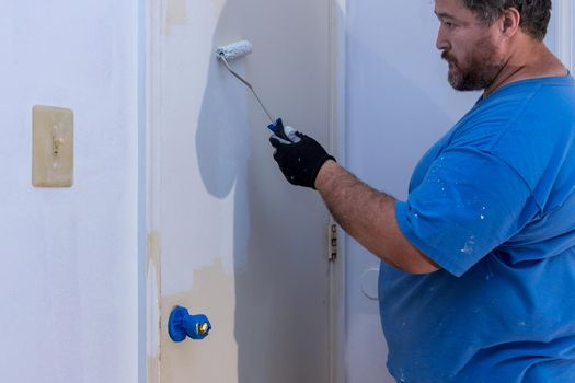Worker painting using paint roller on layer white color a door frame trim