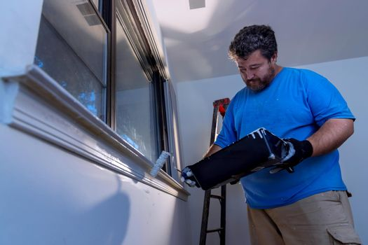 Worker painting using paint roller on layer white color a window frame trim