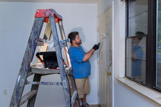 Handyman paints a door molding frame with a paint roller