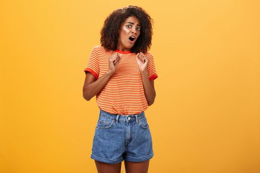 No do not hurt me. Scared silly and insecure good-looking african american woman in stupor screaming for help turning away raising palms near body in defence standing in fright over orange wall