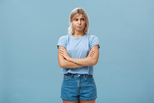 Uncertain troubled and perplexed attractive blond woman with tanned skin holding hands crossed on chest pouting and frowning looking right with worried unsure and doubtful look over blue wall