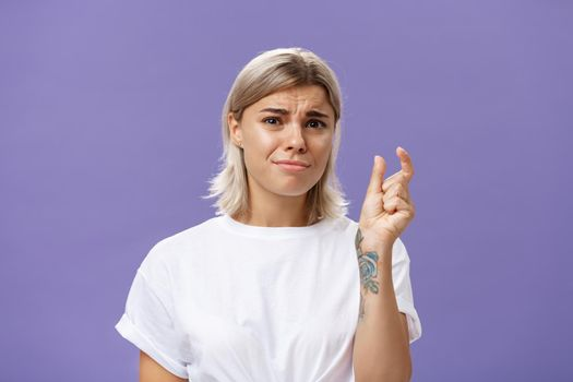 Woman feeling regret lacking small amount of money to afford car. Unhappy displeased good-looking stylish female with tattoos on hands frowning and pursing lips shaping tiny or little object