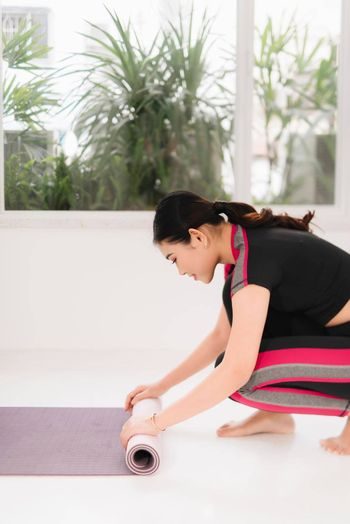 Fitness woman in sports clothing with yoga mat standing in front of window at sunny day