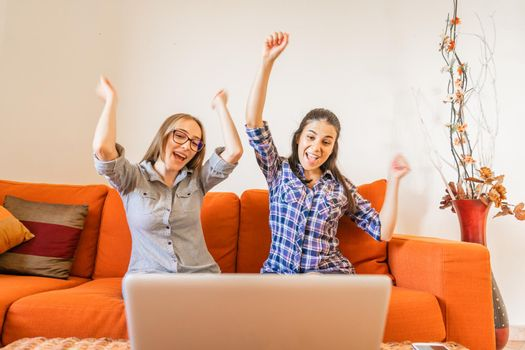 Two very happy girl cheering with hands up looking at laptop screen sitting at home sofa. Young winner women having success in their work. Change your life and make preferred job to live better