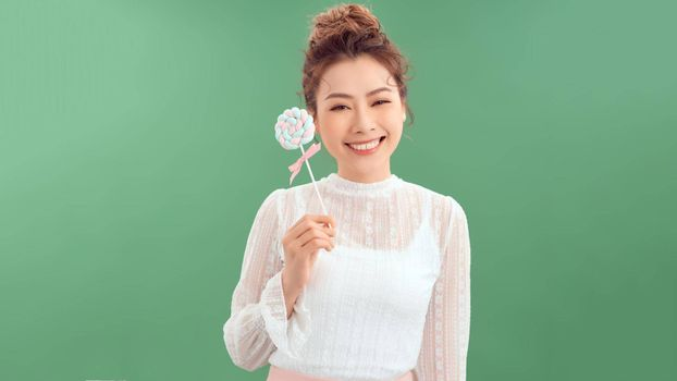 Surprised curly girl eating lollipop. Beauty Model woman holding pink sweet colorful lollipop candy, isolated on green background.