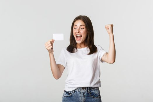 Joyful good-looking girl rejoicing and looking at credit card, fist pump while triumphing, white background