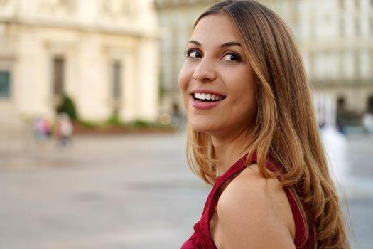 Smart interested young woman turn the head while walking against urban background