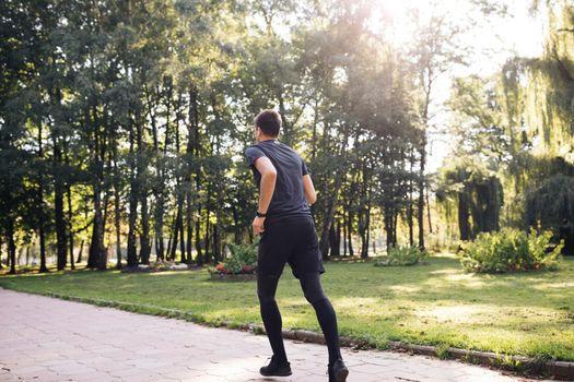 Sportsman Jog Cardio Workout. Runner Fitness Hard Training Before Running Marathon Competition. Running Man Fitness Exercising. Athlete Jogging In Park Preparing Triathlon. Sport Healthy Lifestyle