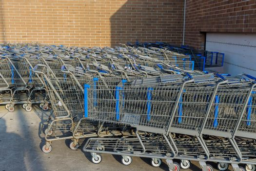 A row of metal carts near a shopping center are placed in a row in a hypermarket