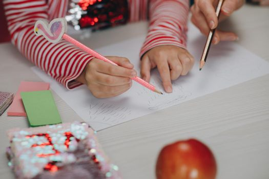 Distance learning online education. Mom does homework with her daughter at home. Distance learning online education. Hands of kid who is involved by drawing
