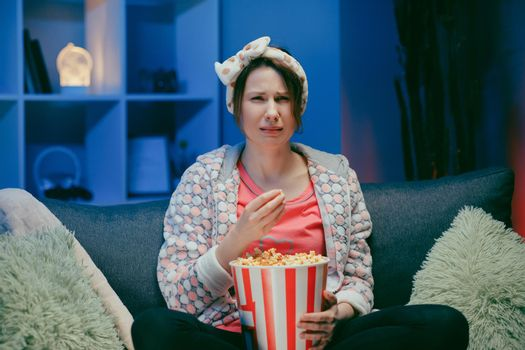 Young woman cry while watching a very moving movie with popcorn at night