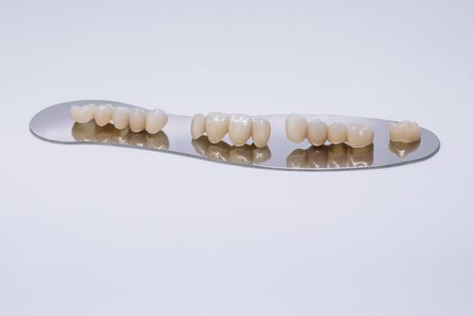 Zirconium tooth crown isolate on wite background. Aesthetic restoration of tooth loss. Ceramic zirconium in final version. Metal Free Ceramic Dental Crowns
