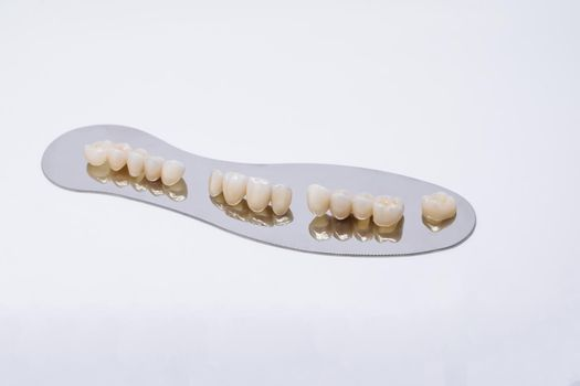 Ceramic zirconium in final version. Metal Free Ceramic Dental Crowns. Zirconium tooth crown. Isolate on background. Aesthetic restoration of tooth loss
