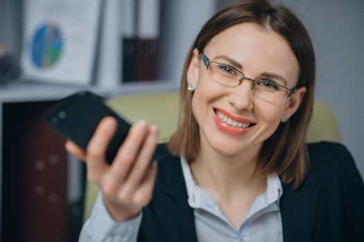 Success and achievement concept. Woman celebrating success in office. Professional female employer receiving good news excited happy cheerful smiling.