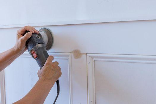 Professional worker polishing sanding the molding trim