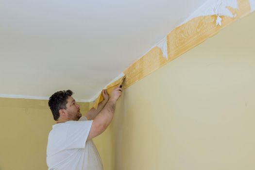 Using a scraper to remove a wallpaper place renovation at home