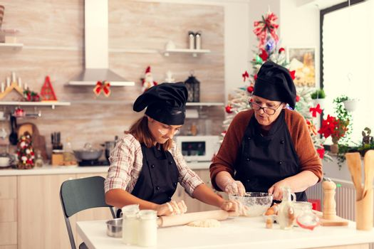 Niece and grandmother wearing apron on christmas day knead dough